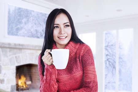 chaud froid: Belle jeune femme r�chauffer avec une tasse de caf� chaud pr�s de la chemin�e � la maison