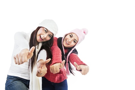 Two friends give thumbs up wearing winter clothes isolated in white photo