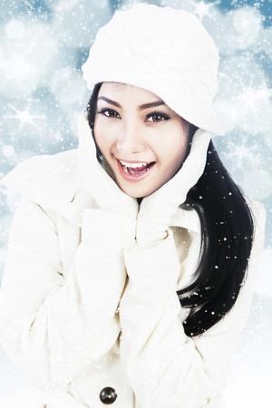 ropa de invierno: Hermosa mujer joven con ropa de invierno y guantes blancos sobre fondo azul defocused luces Foto de archivo