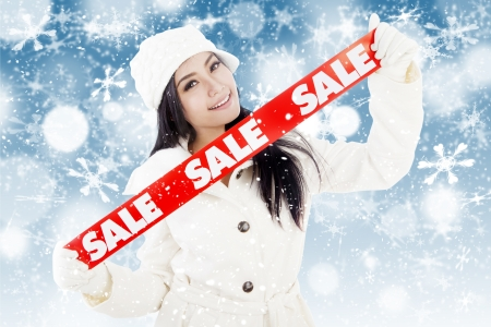 overcoat: Portrait of fashionable woman showing banner of winter sale  isolated on white background Stock Photo