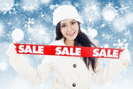 promotion girl: Portrait of fashionable woman showing banner of winter sale  isolated on white background Stock Photo
