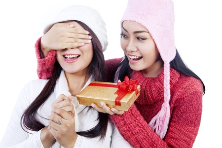 Beautiful woman is giving her friend a christmas gift surprise isolated in white photo