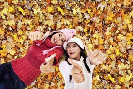 fashion photography: Two friends are laying on Autumn leaves Stock Photo