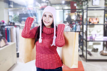 Beautiful woman with beany and jumper carry brown shopping bags in the mall photo