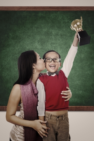 proud: A smart boy is raising a trophy while his mother is kissing him in the classroom Stock Photo