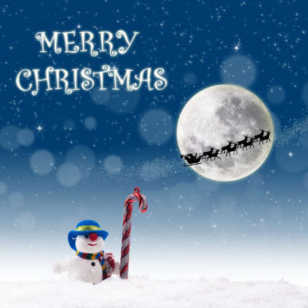 photoshop: Christmas card design with snowman and candy cane under full moon  on blue background