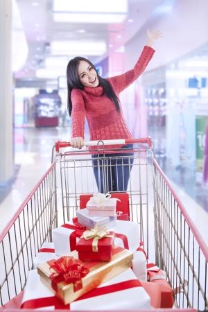 cajas navide�as: El cabello largo mujer con cajas de Navidad en el carro de compras est� en el centro comercial Foto de archivo
