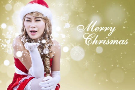 Mrs Claus giving Christmas greeting in Santa clothes costume on golden lights background photo