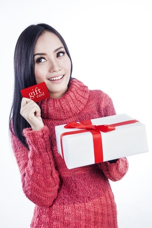 Woman showing  gift card while holding white present isolated in white photo