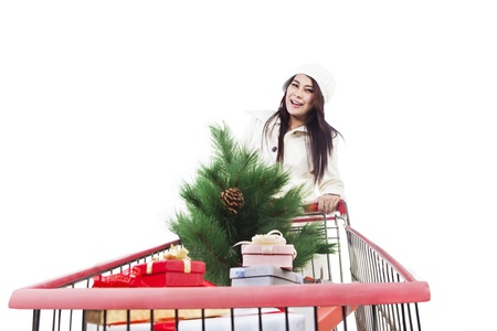 Woman is shopping for Christmas tree and boxes inside a trolley, isolated in white Stock Photo - 16251233