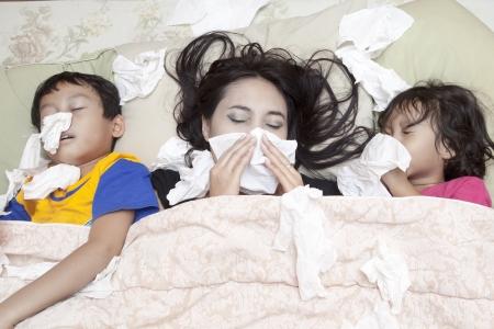estornudo: Familia está acostado en una cama debido a la gripe en invierno Foto de archivo