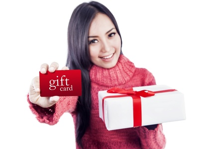 gift wrapping: Asian woman is showing a gift card while holding a present