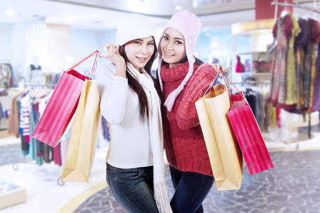 Two happy friends are shopping together in the mall photo
