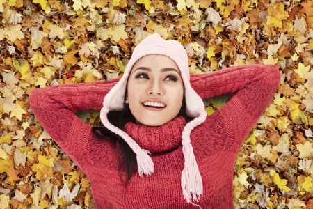 Happy Asian woman laying on Autumn leaves in the park photo