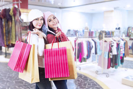 Two friends who love shopping are holding bags in front of the mall photo