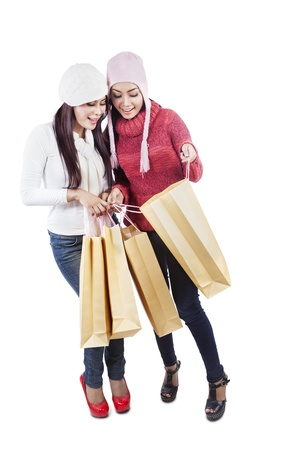 Two Asian women are looking inside brown shopping bags, isolated in white photo