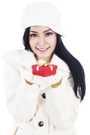 Portrait of beautiful woman winter clothes giving a christmas gift  isolated on white background photo