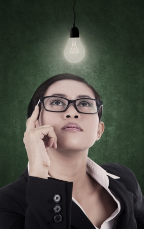 lit lamp: Business woman is looking up at the lit lamp representing that she