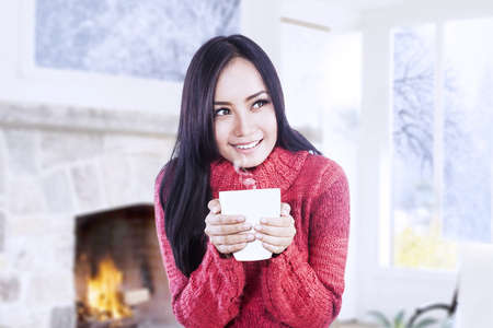 Beautiful girl is warming near fireplace while holding a cup of coffee in her hands photo