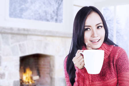 Beautiful young woman enjoying her coffee at home near fireplace photo