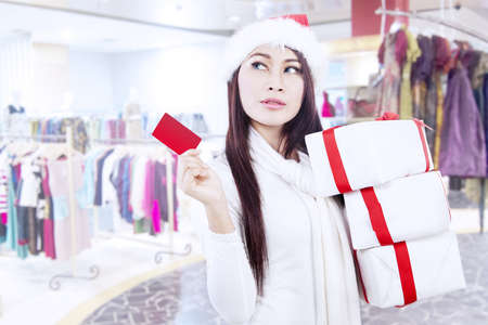 Attractive young woman wearing Santa hat is holding a gift card and lots of white boxes in the mall photo