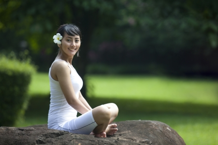 Asian female looking at the camera while sitting on the stone looking at the camera in the park photo