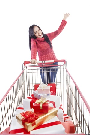 trolley: Beautiful lady with christmas gifts inside a trolley, isolated in white Stock Photo
