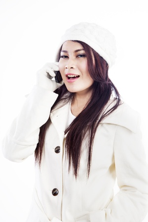 A happy customer with winter suit is calling using her phone, isolated in white photo