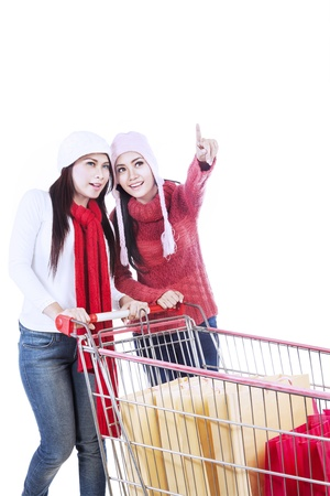 Two happy customers are pushing a trolley while pointing at something, isolated in white photo