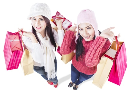 Two happy friends do shopping together, isolated in white photo