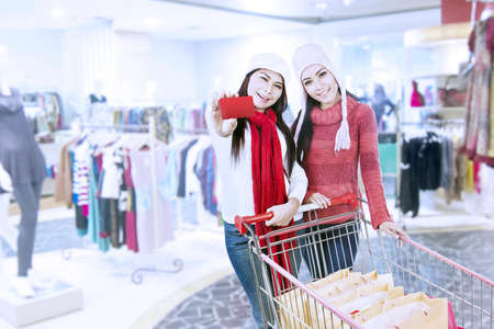 Two friends are shopping with trolley at the mall photo