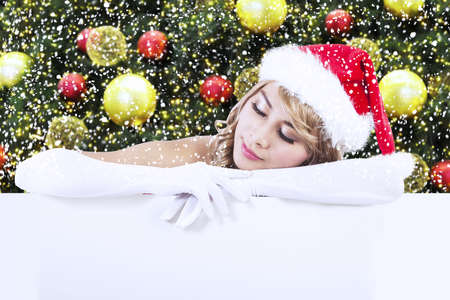 Christmas woman with blank sign billboard in front of christmas tree Stock Photo - 16494345