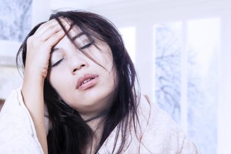 fieber: Asiatische Frau mit Kopfschmerzen mit Fieber zu Hause Lizenzfreie Bilder