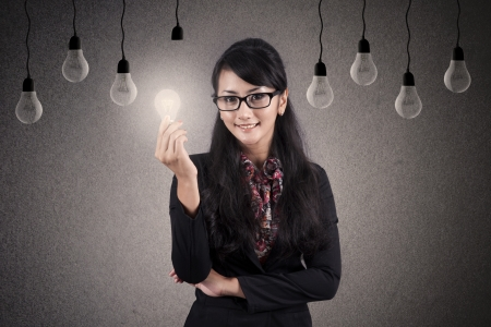 Beautiful Asian Businesswoman with glasses holds bright lightbulb photo
