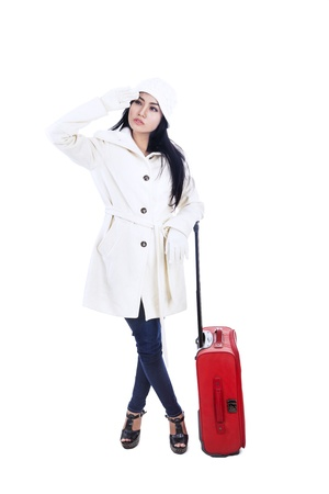 Beautiful young woman traveller with red suitcase is ready for winter holidays photo