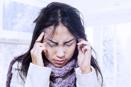 Woman having terrible headache in winter photo