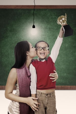 mom kiss son: A mother is kissing her son for winning a trophy at school Stock Photo