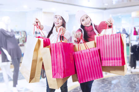 Two friends are shopping in winter time at the mall photo