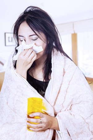 sneezing: Una donna sta soffiando il naso avvolto in coperta a casa