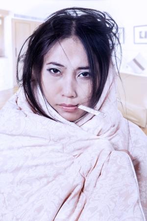 fieber: Frau mit Fieber in Decke geh�llt beim Bei�en ein Thermometer in den Mund