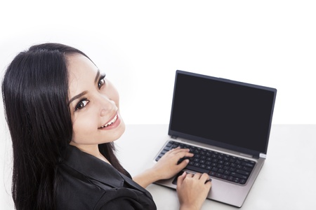 Attractive woman is smiling at the camera while doing online shopping, isolated over white Stock Photo - 16634123