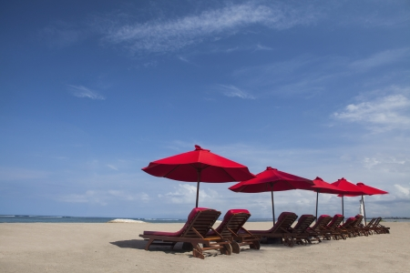 Many chairs and red umbrellas at the beach in Asia photo