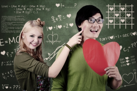 s horn: Beautiful nerd girl is teasing her guy whose holding red heart at school
