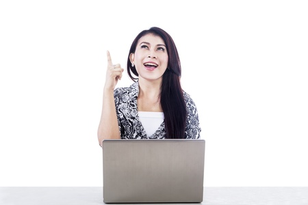 netbook: Beautiful woman having a bright idea by pointing her finger while working with her laptop isolated over white Stock Photo