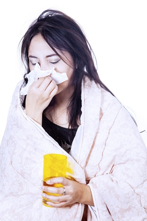 A woman is blowing her nose with tissue while holding a yellow glass, isolated in white photo