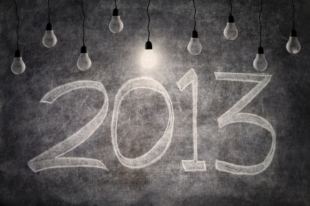 Bright ideas of 2013 represent by light bulbs on blackboard background photo