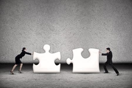 두 비즈니스 사람들이 성공하기 위해 두 개의 퍼즐을 넣어 함께 노력하고 있습니다
