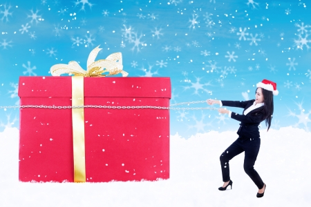 Businesswoman is holding a christmas gift box with chain under the snow on blue background Stock Photo - 16634115