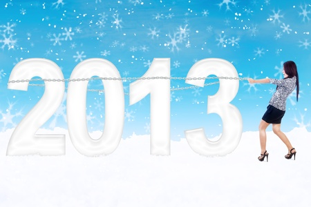 Businesswoman is holding 2013 with chain on blue background while snowing photo