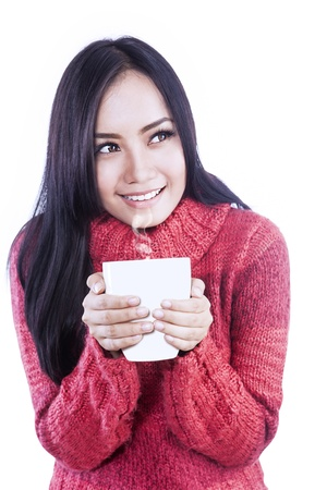 Happy woman is holding a cup of coffee in her hands, isolated in white photo